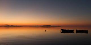 Un coucher du soleil chaud sur une eau calme, avec des îles à l'arrière-plan Image libre de droits
