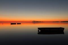 Un coucher du soleil chaud sur une eau calme, avec des îles à l'arrière-plan Photos libres de droits
