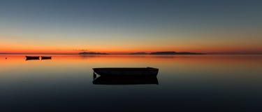 Un coucher du soleil chaud sur une eau calme, avec des îles à l'arrière-plan Photographie stock libre de droits