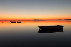 Un coucher du soleil chaud sur une eau calme, avec des îles à l'arrière-plan Photographie stock