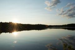 Un coucher du soleil d'automne transforme un lac en miroir Images stock