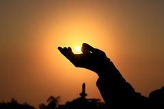 Un coup de silhouette essaye de toucher le Sun Image libre de droits
