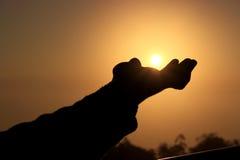 Un coup de silhouette essaye de toucher le Sun Images libres de droits