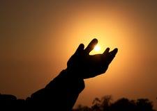 Un coup de silhouette essaye de toucher le Sun Photographie stock libre de droits