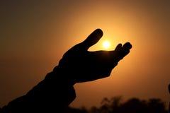 Un coup de silhouette essaye de toucher le Sun Images stock
