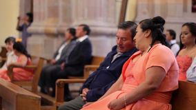 Un couple écoutant la masse dans une église pendant une célébration de mariage banque de vidéos