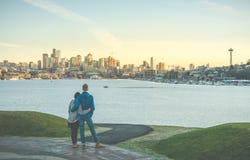 Un couple étreint et regardant le paysage urbain de Seattle avec le coucher du soleil, Seattle, Washington, Etats-Unis Photo stock