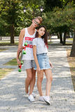 Un couple adolescent à la mode posant sur un fond brouillé de parc Début d'une histoire d'amour Sentiments, concept de tendresse Photos stock