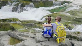 Un couple affectueux admire la belle rivière de montagne Ils se reposent côte à côte sur une roche, l'eau bouillonne autour banque de vidéos