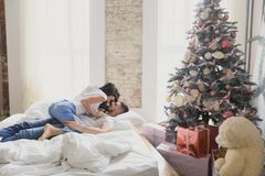 Un couple affectueux célèbre Noël ensemble Amants sur un lit de grenier Photos stock