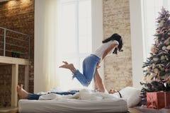 Un couple affectueux célèbre Noël ensemble Amants sur un lit de grenier Photographie stock libre de droits