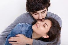 Un couple affectueux d'isolement au-dessus du fond blanc Un jeune type embrassant et embrassant son amie Relations sensuelles ent Photographie stock