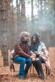 Un couple affectueux dans la forêt, couverte de plaid, regardant l'un l'autre avec un sourire outdoors Photographie stock libre de droits