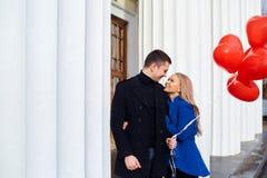 Un couple affectueux dans un manteau avec les coeurs rouges de ballons dans des mains Photo libre de droits