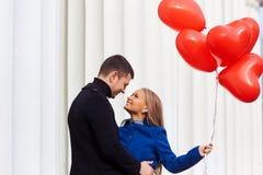 Un couple affectueux dans un manteau avec les coeurs rouges de ballons dans des mains Image libre de droits