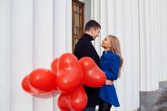 Un couple affectueux dans un manteau avec les coeurs rouges de ballons dans des mains Photographie stock libre de droits