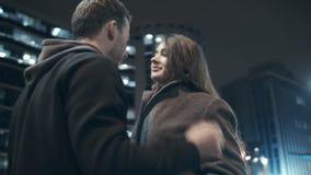 Un couple affectueux dans une ville de nuit Le type prend soin d'amie se boutonnant vers le haut de son manteau ainsi elle ne gèl banque de vidéos