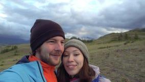 Un couple affectueux fait le selfie sur les montagnes Couples de touristes de jeune métis faisant à Selfie drôle la causerie visu banque de vidéos