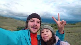 Un couple affectueux fait le selfie sur les montagnes Couples de touristes de jeune métis faisant à Selfie drôle la causerie visu clips vidéos