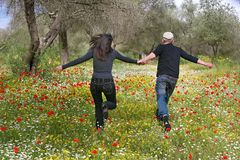 Un couple affectueux fonctionnant le long du gisement de fleur photographie stock