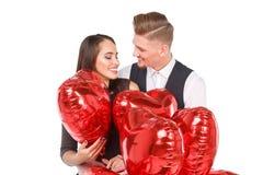 Un couple affectueux s'amuse se tenant parmi les boules D'isolement sur le fond blanc Photographie stock