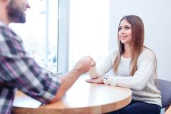 Un couple affectueux se reposant dans un café, tenant des mains et regardant affectueusement l'un l'autre Image libre de droits