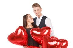 Un couple affectueux se tient parmi les boules sous forme de coeur et étreinte D'isolement sur le blanc Image libre de droits