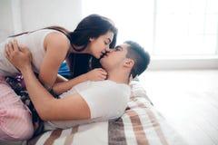 Un couple affectueux se trouve sur le lit Chambre à coucher lumineuse et confortable Confort et amour de famille Image stock