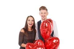Un couple affectueux, support parmi les ensembles de boules rouges d'hélium et rit heureusement D'isolement sur le fond blanc Image stock