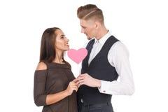 Un couple affectueux, tenant un coeur sur un bâton et regardant l'un l'autre D'isolement Photos stock