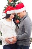 Un couple attendant le bébé à Noël près de l'arbre Images libres de droits