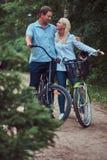 Un couple attrayant d'une femelle et d'un homme blonds s'est habillé dans des vêtements sport sur un tour de bicyclette avec leur Images stock