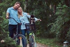 Un couple attrayant d'une femelle et d'un homme blonds s'est habillé dans des vêtements sport sur un tour de bicyclette avec leur Image stock