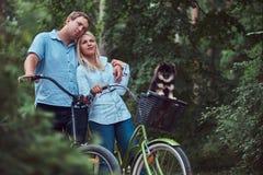 Un couple attrayant d'une femelle et d'un homme blonds s'est habillé dans des vêtements sport sur un tour de bicyclette avec leur Photos stock