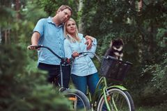 Un couple attrayant d'une femelle et d'un homme blonds s'est habillé dans des vêtements sport sur un tour de bicyclette avec leur Photo libre de droits