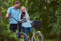 Un couple attrayant d'une femelle et d'un homme blonds s'est habillé dans des vêtements sport sur un tour de bicyclette avec leur Photos libres de droits