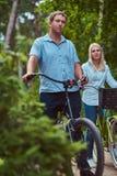 Un couple attrayant d'une femelle et d'un homme blonds s'est habillé dans des vêtements sport sur un tour de bicyclette en parc Photographie stock libre de droits