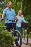 Un couple attrayant d'une femelle et d'un homme blonds s'est habillé dans des vêtements sport sur un tour de bicyclette en parc Images stock