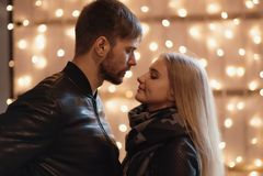 Un couple attrayant dans l'amour embrasse et apprécie un moment intime ensemble, contre le contexte des lumières de ville Photographie stock libre de droits