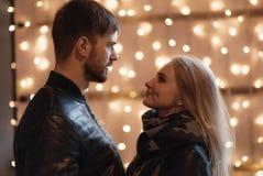Un couple attrayant dans l'amour embrasse et apprécie un moment intime ensemble, contre le contexte des lumières de ville Photo libre de droits
