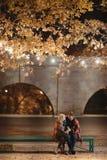 Un couple attrayant dans l'amour embrasse et apprécie un moment intime ensemble, contre le contexte des lumières de ville Image libre de droits