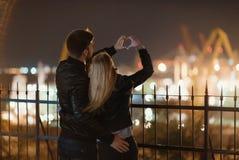 Un couple attrayant dans l'amour embrasse et apprécie un moment intime ensemble, contre le contexte des lumières de ville Photo stock