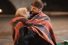 Un couple attrayant dans l'amour embrasse et apprécie un moment intime ensemble, contre le contexte des lumières de ville Images libres de droits