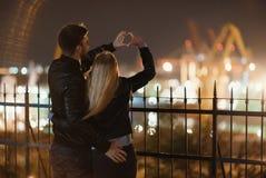 Un couple attrayant dans l'amour embrasse et apprécie un moment intime ensemble, contre le contexte des lumières de ville Image stock
