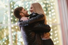Un couple attrayant dans l'amour embrasse et apprécie un moment intime ensemble, contre le contexte des lumières de ville Photographie stock
