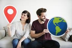 Un couple blanc d'envie de voyager tenant des icônes Photographie stock