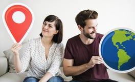 Un couple blanc d'envie de voyager tenant des icônes Images stock