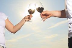 Un couple buvant une bouteille de vin rouge dehors Images stock