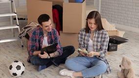 Un couple comptant l'argent et notant leurs dépenses en bloc-notes housewarming clips vidéos