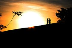 Un couple contre le coucher du soleil photo stock